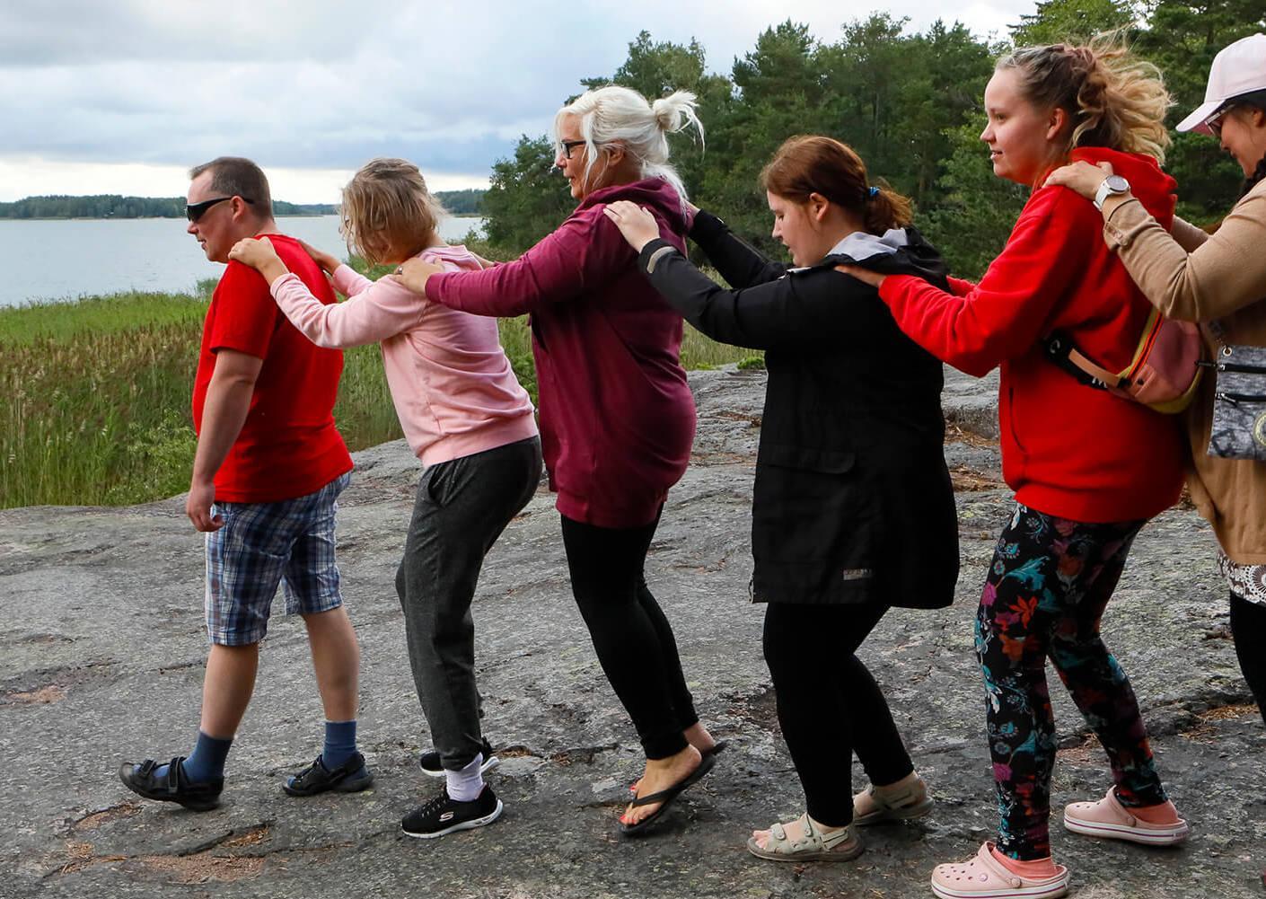 Ihmiset tanssivat letkajenkkaa rantakalliolla
