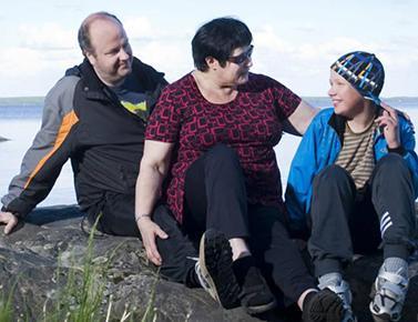 perhe istuu kalliolla